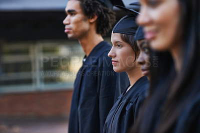 Buy stock photo A group of solemn college graduates lined up at graduation