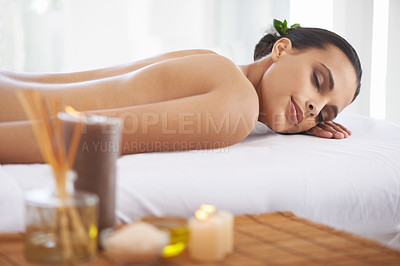 Buy stock photo A young woman lying in a health sap surrounded by scented candles