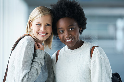 Buy stock photo Two young college students standing together and smiling