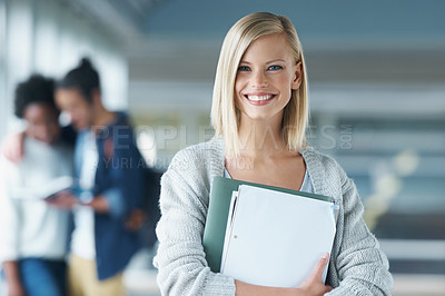 Buy stock photo Portrait of an attractive young college student holding books and standing in a hallway