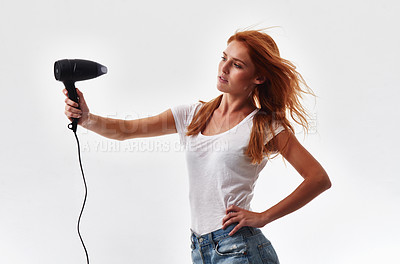 Buy stock photo Shot of a beautiful young woman blow drying her hair against a white background