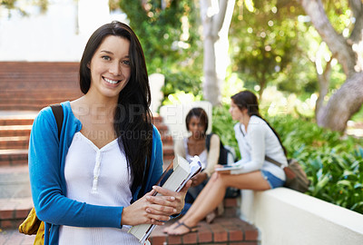 Buy stock photo Cropped young student standing out on campus with her classmates in the background