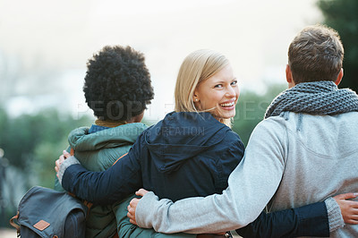 Buy stock photo Shot of a group of college friends walking arm in arm outside