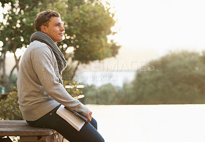 Buy stock photo Shot of a thoughtful young male student leaning on a campus bench