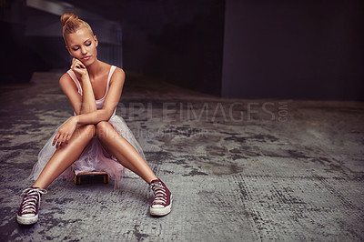 Buy stock photo A young woman wearing a ballet tutu and sneakers sitting on a concrete floor