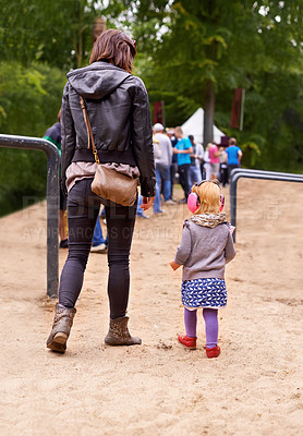 Buy stock photo Rearview shot of a mother and daughter queueing up for a festival