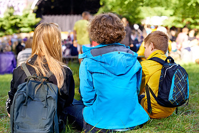Buy stock photo Rearview shot of three children sitting on the grass during a concert