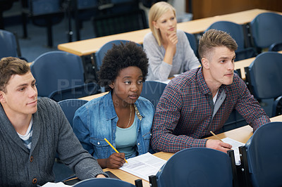 Buy stock photo A group of students in their  Lecture taking notes and paying attention