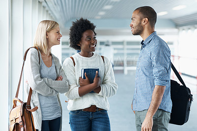 Buy stock photo Shot of university students talking to each other while waiting for a class
