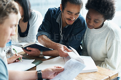 Buy stock photo Shot of a study group going over work in their textbook
