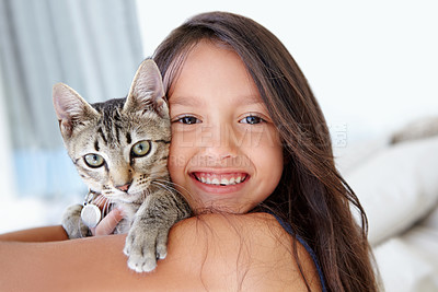 Buy stock photo A young girl smiling at the camera while holding her cat