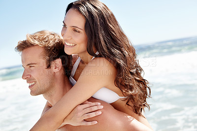 Buy stock photo Shot of a handsome young piggybacking his wife at the beach