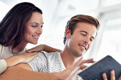Buy stock photo An attractive couple browsing on a digital tablet