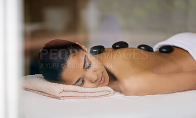Buy stock photo Shot of a young woman enjoying a hot rock treatment at a spa