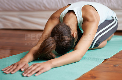 Buy stock photo An attractive young woman working out at home