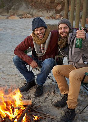 Buy stock photo Two young men sitting around a fire on the beach