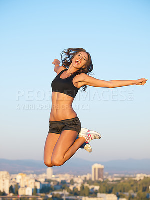 Buy stock photo A young woman in exercise wear jumping in the air with a cityscape in the background