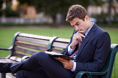 Buy stock photo Shot of a thoughtful-looking businessman sitting on a park bench