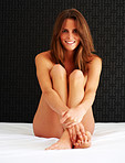 Happy young naked female sitting on the bed