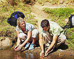 Active couple on a hiking  expedition  getting a drink