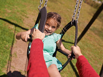 Buy stock photo Shot of a little girl being pushed on a swing outside