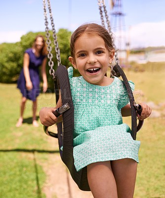 Buy stock photo Shot of a young girl playing on a swing outsdie