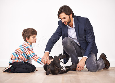 Buy stock photo A father and son petting a dog together