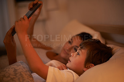 Buy stock photo A mother reading a bedtime story to her son from a digital tablet
