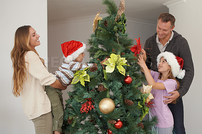 Buy stock photo Shot of a young boy decorating a christmas tree along with his family