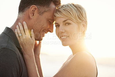 Buy stock photo Closeup of a woman holding her husband while they stand outside