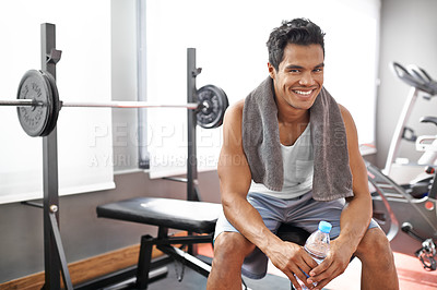Buy stock photo A young ethnic man smiling while sitting on a weight bench at the gym