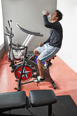 Buy stock photo A young man sitting on an exercise bike and drinking water