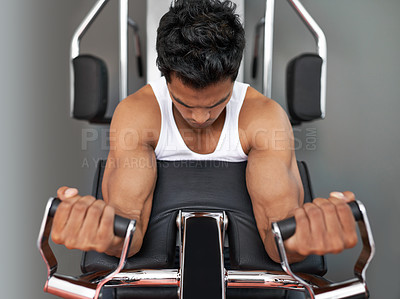 Buy stock photo Low-angle view of a young ethnic man working out at the gym