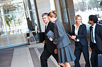 Group of business colleagues walking into their office building