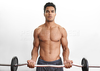Buy stock photo Studio portrait of an athletic young man lifting a barbell