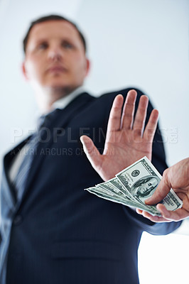 Buy stock photo Low-angle view of a businessman refusing a bribe