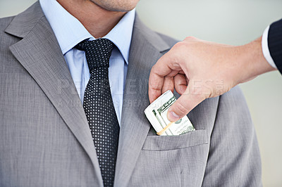 Buy stock photo Cropped studio shot of money being placed in a businessman's pocket