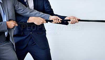 Buy stock photo Studio shot of two businessmen pulling on a rope