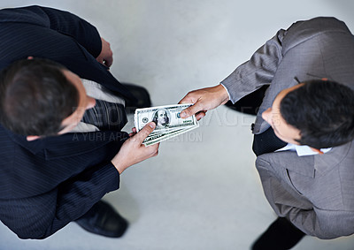 Buy stock photo Two businessmen exchanging cash