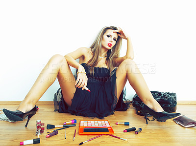 Buy stock photo A woman sitting on the floor among her makeup products
