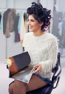 Buy stock photo A young model reading a magazine at the hair salon
