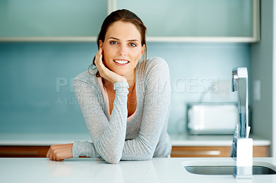 Buy stock photo Relaxed young woman standing at the kitchen counte