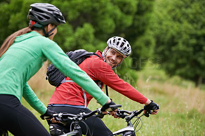 Buy stock photo A couple looking at each other while biking together in the outdoors
