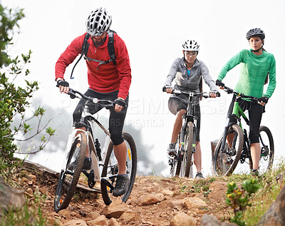 Buy stock photo A group of mountain bikers making their way across a rocky hillside