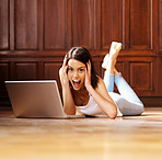 Surprised - Young woman using laptop at home