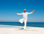 Full length image of a mature man practicing yoga at the sea shore