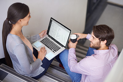 Buy stock photo Shot of two young office workers sitting in a stairwell using a laptop