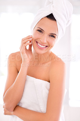 Buy stock photo A beautiful woman touching her skin while standing wrapped in her towel
