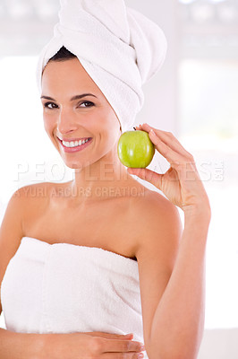 Buy stock photo A beautiful woman holding up a green apple next to her face