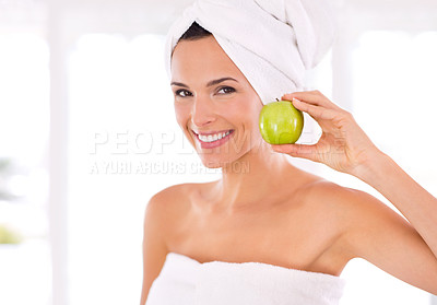 Buy stock photo Portrait of a beautiful woman holding up an apple next to her face